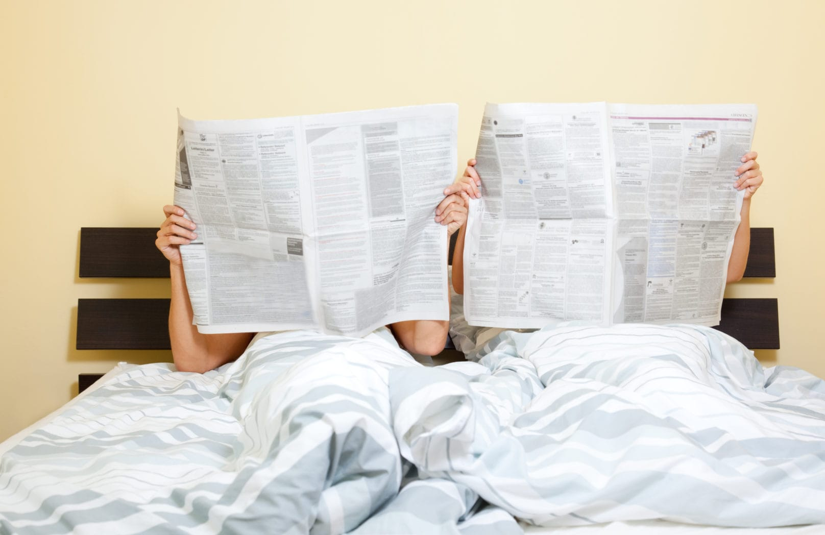 Two people reading paper in bed