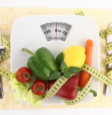 Vegetables and tape measure on scales