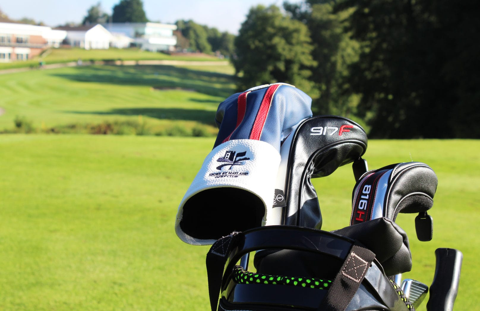 Close up of golf club covers with course in background