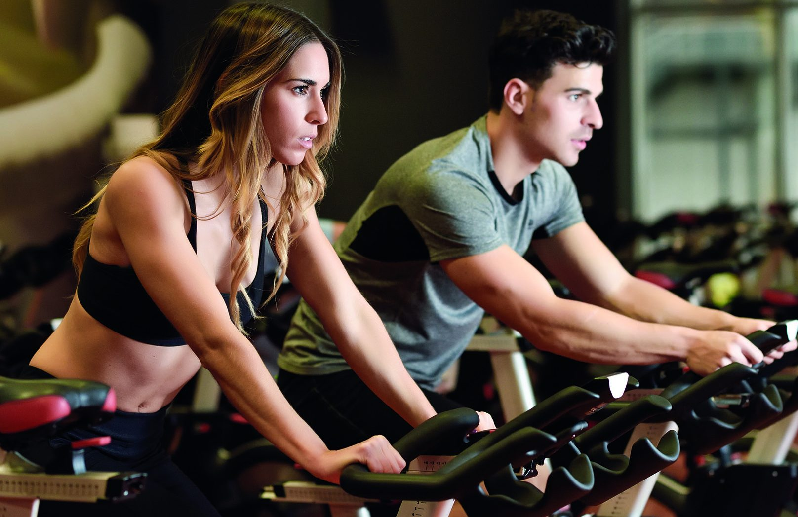 Woman and man on spinning bikes - Peake Fitness
